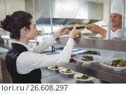 Купить «Chef handing food dish to waitress at order station», фото № 26608297, снято 13 марта 2017 г. (c) Wavebreak Media / Фотобанк Лори