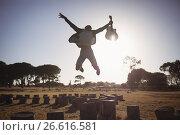 Купить «Happy man holding guitar while jumping against clear sky», фото № 26616581, снято 9 марта 2017 г. (c) Wavebreak Media / Фотобанк Лори