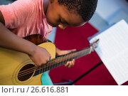 Купить «High angle view of boy playing guitar», фото № 26616881, снято 11 марта 2017 г. (c) Wavebreak Media / Фотобанк Лори