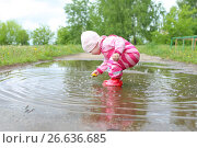 1 years baby girl plays in puddle after rain. Стоковое фото, фотограф ivolodina / Фотобанк Лори