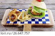 Купить «Hamburger, onion ring and french fries on chopping board», видеоролик № 26647757, снято 14 декабря 2019 г. (c) Wavebreak Media / Фотобанк Лори