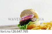 Купить «Hamburger and french fries on chopping board», видеоролик № 26647765, снято 14 декабря 2019 г. (c) Wavebreak Media / Фотобанк Лори