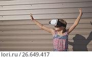 Купить «Happy amazed little girl wearing virtual reality goggles watching movies or playing video games. Cheerful surprised child looking in VR glasses. On a striped background.», видеоролик № 26649417, снято 10 июля 2017 г. (c) Mikhail Davidovich / Фотобанк Лори