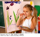 Купить «Child painting finger on easel. Group of kids with teacher.», фото № 26652445, снято 25 марта 2017 г. (c) Gennadiy Poznyakov / Фотобанк Лори