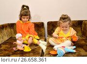 Купить «Две маленькие сестренки играют с куклами на диване», фото № 26658361, снято 26 марта 2016 г. (c) Ирина Борсученко / Фотобанк Лори
