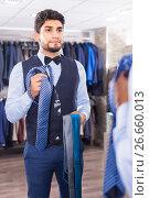 Купить «Man is picking up tie for waistcoat in front of the mirror», фото № 26660013, снято 20 июня 2017 г. (c) Яков Филимонов / Фотобанк Лори