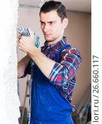 Купить «positive professional builder drilling hole in wall with perforator», фото № 26660117, снято 21 мая 2017 г. (c) Яков Филимонов / Фотобанк Лори