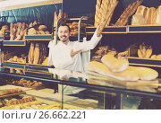 Купить «Male shop assistant demonstrating delicious loaves of bread in bakery», фото № 26662221, снято 26 января 2017 г. (c) Яков Филимонов / Фотобанк Лори