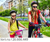 Купить «Bicycle path with children. Girls wearing helmet with rucksack .», фото № 26666449, снято 9 апреля 2016 г. (c) Gennadiy Poznyakov / Фотобанк Лори