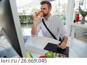 Купить «Designer having drink writing on graphics tablet», фото № 26669045, снято 26 марта 2017 г. (c) Wavebreak Media / Фотобанк Лори
