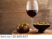 Купить «Olives served in bowls by wineglass on table», фото № 26669837, снято 15 февраля 2017 г. (c) Wavebreak Media / Фотобанк Лори