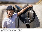 Купить «Smiling rider standing with his hand on white horse», фото № 26671961, снято 28 марта 2017 г. (c) Wavebreak Media / Фотобанк Лори