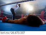 Купить «Unconscious boxer lying by referee in ring», фото № 26673337, снято 22 января 2017 г. (c) Wavebreak Media / Фотобанк Лори
