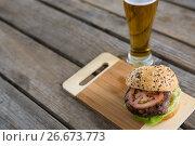 Купить «High angle view of hamburger on cutting board by beer», фото № 26673773, снято 13 января 2017 г. (c) Wavebreak Media / Фотобанк Лори