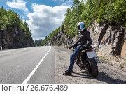 Купить «Водитель мотоцикла отдыхает на обочине горной дороги в ясный солнечный день», фото № 26676489, снято 14 июля 2017 г. (c) Кекяляйнен Андрей / Фотобанк Лори