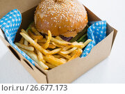Купить «Close up of hamburger with French fries in box», фото № 26677173, снято 13 января 2017 г. (c) Wavebreak Media / Фотобанк Лори