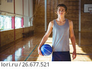 Купить «Portrait of smiling young man with basketball standing in court», фото № 26677521, снято 18 февраля 2017 г. (c) Wavebreak Media / Фотобанк Лори
