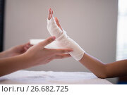 Купить «Close-up of female therapist wrapping bandage on hand», фото № 26682725, снято 23 апреля 2017 г. (c) Wavebreak Media / Фотобанк Лори