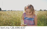 Купить «A young girl is given banknotes of dollars and she is very happy about it against a background of nature in a warm sunny day. Money, finances and people concept - smiling little european girl with dollar cash money», видеоролик № 26690637, снято 18 июля 2017 г. (c) Mikhail Davidovich / Фотобанк Лори