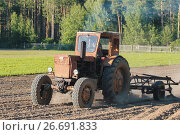 Купить «Preparing land with seedbed cultivator - tractor on field, agricultural works at farmlands», фото № 26691833, снято 29 июня 2017 г. (c) Константин Шишкин / Фотобанк Лори