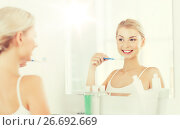 Купить «woman with toothbrush cleaning teeth at bathroom», фото № 26692669, снято 13 февраля 2016 г. (c) Syda Productions / Фотобанк Лори