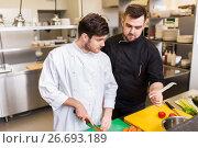 Купить «two chefs cooking food at restaurant kitchen», фото № 26693189, снято 2 апреля 2017 г. (c) Syda Productions / Фотобанк Лори