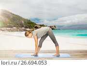 Купить «woman making yoga intense stretch pose on beach», фото № 26694053, снято 13 ноября 2015 г. (c) Syda Productions / Фотобанк Лори