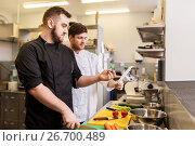 Купить «two chefs cooking food at restaurant kitchen», фото № 26700489, снято 2 апреля 2017 г. (c) Syda Productions / Фотобанк Лори
