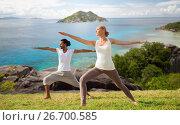 Купить «couple making yoga in warrior pose at seaside», фото № 26700585, снято 6 августа 2014 г. (c) Syda Productions / Фотобанк Лори