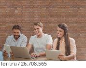 Купить «Happy business people at a desk looking at a computer and a tablet against brick wall», фото № 26708565, снято 21 сентября 2019 г. (c) Wavebreak Media / Фотобанк Лори