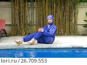 Купить «Attractive woman in a Muslim swimwear burkini  on a pool side in a tropical garden», фото № 26709553, снято 9 марта 2017 г. (c) Куликов Константин / Фотобанк Лори