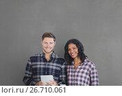 Купить «Happy business people holding a tablet against grey background», фото № 26710061, снято 4 июня 2020 г. (c) Wavebreak Media / Фотобанк Лори