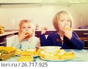 Купить «Children eat cakes at kitchen», фото № 26717925, снято 14 декабря 2018 г. (c) Яков Филимонов / Фотобанк Лори