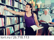 Купить «Young female is choosing new novel for buying», фото № 26718113, снято 28 июня 2017 г. (c) Яков Филимонов / Фотобанк Лори