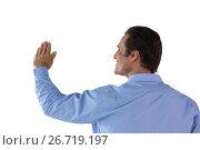 Купить «Rear view of mature businessman touching invisible interface», фото № 26719197, снято 19 января 2017 г. (c) Wavebreak Media / Фотобанк Лори