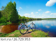 Купить «The bike is on the lake on Sunny summer day», фото № 26729953, снято 6 июня 2017 г. (c) Алексей Маринченко / Фотобанк Лори