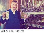 Купить «man seller wearing uniform having metal furniture in hands in store», фото № 26730149, снято 22 мая 2019 г. (c) Яков Филимонов / Фотобанк Лори