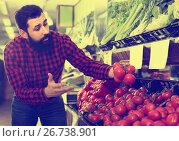 Smiling male seller showing fresh tomatoes in shop, фото № 26738901, снято 15 ноября 2016 г. (c) Яков Филимонов / Фотобанк Лори