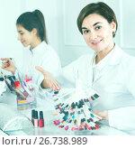 Купить «Female manicurist showing lacquer color schemes», фото № 26738989, снято 2 февраля 2017 г. (c) Яков Филимонов / Фотобанк Лори
