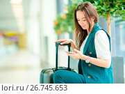Купить «Portrait of young woman with smartphone in international airport. Airline passenger in an airport lounge waiting for flight aircraft», фото № 26745653, снято 13 июля 2017 г. (c) Дмитрий Травников / Фотобанк Лори