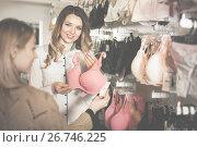 Купить «Female seller demonstrating client bras in underwear store», фото № 26746225, снято 20 марта 2017 г. (c) Яков Филимонов / Фотобанк Лори