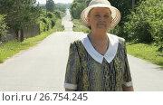 Купить «Old woman walking on the road at the sunny day», видеоролик № 26754245, снято 25 июля 2017 г. (c) worker / Фотобанк Лори
