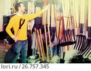 Купить «Man choosing new shovel in garden equipment shop», фото № 26757345, снято 2 марта 2017 г. (c) Яков Филимонов / Фотобанк Лори