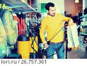Купить «Young man choosing garden sprayer in garden equipment shop», фото № 26757361, снято 2 марта 2017 г. (c) Яков Филимонов / Фотобанк Лори