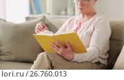 Купить «senior woman in glasses reading book at home», видеоролик № 26760013, снято 27 января 2020 г. (c) Syda Productions / Фотобанк Лори