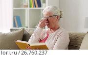 Купить «senior woman in glasses reading book at home», видеоролик № 26760237, снято 25 июня 2017 г. (c) Syda Productions / Фотобанк Лори