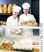 Male and female staff offering fresh baguettes. Стоковое фото, фотограф Яков Филимонов / Фотобанк Лори