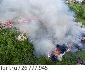 Купить «Вид сверху на горящие деревянные постройки и автомобили пожарной команды», фото № 26777945, снято 13 июля 2017 г. (c) Кекяляйнен Андрей / Фотобанк Лори