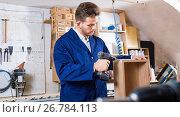 Купить «Male worker finishing to drill drawer», фото № 26784113, снято 7 ноября 2016 г. (c) Яков Филимонов / Фотобанк Лори