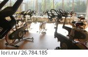 Купить «Bicycling simulators in the gym, interior of modern fitness club, slider shot», видеоролик № 26784185, снято 27 апреля 2018 г. (c) Константин Шишкин / Фотобанк Лори